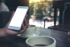 Uma mão do ` s da mulher que guarda o telefone celular branco com a tela vazia do desktop com os copos de café na tabela de madei Fotografia de Stock