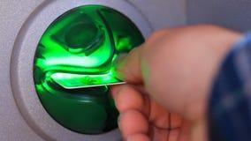 Uma mão do ` s da pessoa toma o cartão de crédito fora do ATM Vídeo do close-up filme