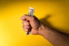 Uma mão do ` s do homem guarda para fora dólares Mão e dinheiro em um fundo amarelo Falta de dinheiro Orçamento de família Imagem de Stock Royalty Free