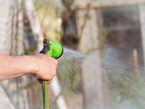 Uma mão do ` s do homem guarda uma mangueira Imagens de Stock Royalty Free