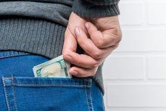 Uma mão do ` s do homem retira dólares do bolso traseiro das calças de brim Imagem de Stock Royalty Free