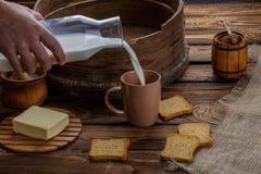 Uma mão do ` s do homem derrama o leite em um copo no fundo da serapilheira e de um fundo de madeira Em torno dos biscoitos dispe imagens de stock royalty free