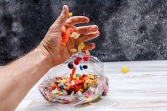 Uma mão do ` s do homem derrama para fora a mistura de doces coloridos em um saco de plástico Fotografia de Stock Royalty Free