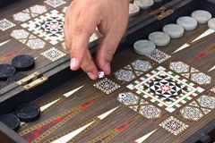 Uma mão do ` s do homem guarda um jogo da gamão imagem de stock