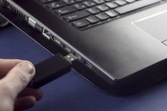 Uma mão do ` s do homem introduz uma movimentação do flash de USB em um usb do portátil imagens de stock