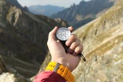 Uma mão do ` s do homem mantém um compasso magnético do bolso para a navegação contra o contexto de uma inclinação rochosa e de u fotos de stock royalty free