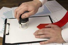 Uma mão do ` s do homem põe um selo sobre uma folha vazia, um laço, uma cópia da lupa fotos de stock royalty free