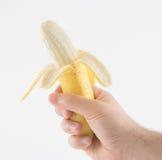 Uma mão e uma banana descascada fotografia de stock royalty free