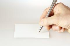 Uma mão está escrevendo Fotografia de Stock