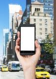 Uma mão está guardando um smartphone com a tela branca do espaço da cópia Fotografia de Stock Royalty Free