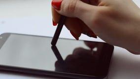 Uma mão fêmea com tratamento de mãos vermelho escreve o texto em uma nota em um smartphone video estoque
