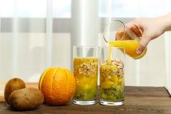 Uma mão fêmea derrama o suco de laranja em um vidro com partes de fruto Imagem horizontal fotos de stock