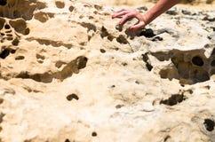 Uma mão fêmea em uma rocha da pedra calcária imagem de stock