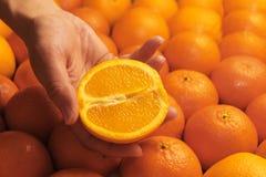Uma mão fêmea guarda a metade de uma laranja Imagem de Stock