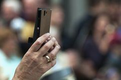 Uma mão fêmea guarda um telefone esperto foto de stock