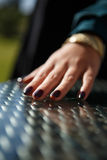 Uma mão fêmea nova com verniz para as unhas glittery escuro Imagem de Stock