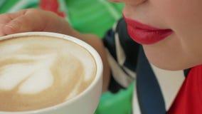 Uma mão fêmea toma um copo do cappuccino perto de seus bordos imagem de stock royalty free