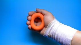 Uma mão ferido que faz exercícios da reabilitação espremendo um anel de aperto da mão filme