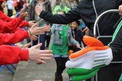 Uma mão gigante nas cores do ireand alcança para fora à multidão no dia do ` s de St Patrick em Dublin Imagens de Stock Royalty Free