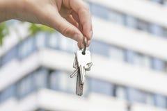 Uma mão guarda as chaves a um apartamento comprado na perspectiva de uma construção do multi-andar imagem de stock royalty free