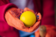Uma mão guarda uma esfera amarela imagens de stock royalty free