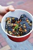 Uma mão Hoiding uma caixa de Fried Stinky Tofu profundo preto foto de stock royalty free