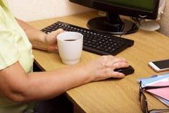 Uma mão idosa da mulher em um rato do computador A avó idosa trabalha atrás do teclado de computador e bebe o café imagem de stock