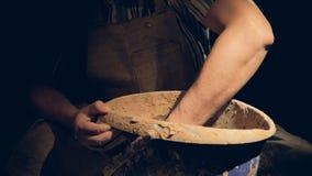 Uma mão masculina dos oleiro move-se lentamente dentro de uma cubeta com argila vídeos de arquivo