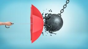 Uma mão masculina que guarda um guarda-chuva vermelho aberto que proteja de uma colisão com uma bola de destruição quebrada foto de stock