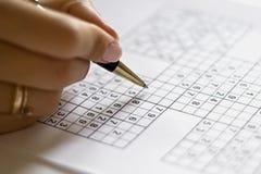 Uma mão na grade do sudoku Fotografia de Stock Royalty Free