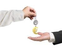 Uma mão que dá o keyring chave do sinal do Euro a uma outra mão Fotos de Stock Royalty Free