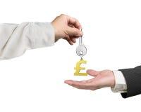 Uma mão que dá o keyring chave a uma outra mão, 3D do símbolo da libra ren Fotografia de Stock Royalty Free