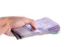 Uma mão que dá uma pilha de ringgit malaio Imagem de Stock Royalty Free