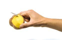 Uma mão que descasca um potatoe Imagens de Stock
