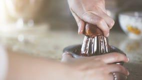Uma mão que espreme o suco de uma laranja em um espremedor de frutas de vidro manual Fotografia de Stock Royalty Free