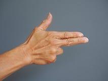 Uma mão que faz uma forma de uma arma aguçado da mão no fundo cinzento Imagem de Stock
