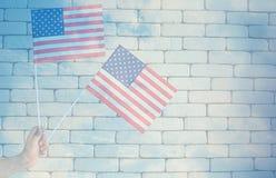 Uma mão que guarda bandeiras americanas dos EUA foto de stock