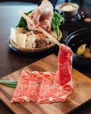 Uma mão que guarda a carne rara superior de Wagyu A5 das fatias com textura alto-marmoreada com os hashis na placa de madeira qua fotografia de stock royalty free
