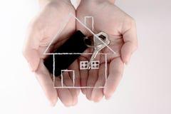 Uma mão que guarda a chave da segurança do alojamento, conceito da segurança fotografia de stock royalty free