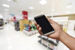 Uma mão que guarda o smartphone na loja borrada da eletrônica Fotografia de Stock
