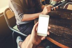 Uma mão que guarda o telefone celular branco com a tela vazia do desktop no café do vintage com uma mulher que usa a tabuleta no  Fotos de Stock Royalty Free