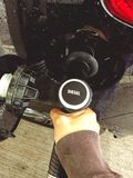 Uma mão que guarda um bocal de combustível e que enche-se acima de um carro com o diesel imagem de stock