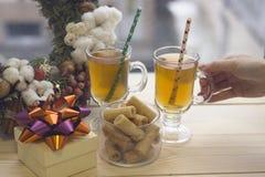 Uma mão que guarda um copo de vidro do chá, de uma caixa de presente, de uma bacia de cookies e de uma grinalda fotografia de stock royalty free