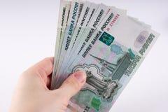Uma mão que guarda uma pilha de mil notas do rublo do dólar Cu do russo Foto de Stock Royalty Free
