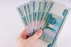 Uma mão que guarda uma pilha de mil notas do rublo do dólar Cu do russo Fotografia de Stock