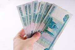 Uma mão que guarda uma pilha de mil notas do rublo do dólar Cu do russo Foto de Stock