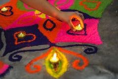 Uma mão que põe uma lâmpada em um rangoli bonito e colorido sobre Diw imagem de stock royalty free