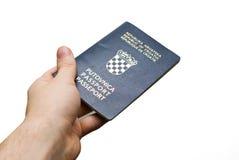 Uma mão que prende um passaporte croata, isolado imagem de stock