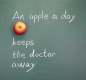 Uma maçã um o dia mantem o doutor ausente fotografia de stock royalty free