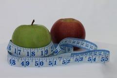 Uma maçã vermelha e verde envolvida em uma fita métrica Imagem de Stock Royalty Free
